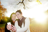 Happy girlfriends with smartphone — Stock Photo