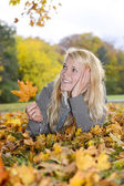 Woman with autumn leave — Stock Photo