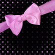 Pink ribbon bow on black background - Foto Stock