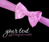 Pink ribbon bow on black background — Photo