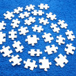 Puzzle on a dark blue fabric - Stock Photo