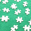 Puzzle on a green fabric - Stock Photo