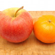 Apple and tangerine on a cutting board — Stock fotografie