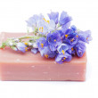 Soap and flowers on white background — Stock Photo