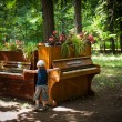 Little boy is playing on two pianos in the park — Foto Stock