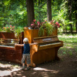 Little boy is playing on two pianos in the park — Lizenzfreies Foto