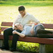 Pregnant woman with her husband in the park — Стоковая фотография