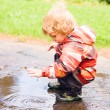A boy plays in a puddle — Stock Photo