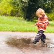 Boy running and jumping in puddles — Stock Photo