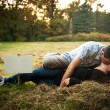 Loving couple lying on the grass and kissing — Stock Photo