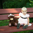 Little girl with teddy bear sitting on the bench — Stockfoto