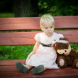 Sad little girl with teddy bear sitting on the bench — Stock Photo
