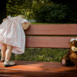 Little girl with a teddy bear is turning his back on the bench — ストック写真