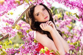 Pretty girl in spring park with pink flowers — Stock Photo