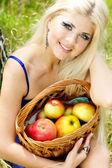 Mujer joven con cesta de manzanas — Foto de Stock