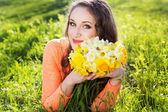 Mutlu gülümseyen kız sarı nergis çiçekleri — Stok fotoğraf