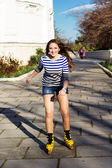 Pretty teenage girl rollerskating in park — Stock Photo