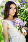 Beautiful girl with a lilac flowers — Photo