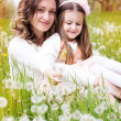 Mother and daughter in field with dandelions — Stock Photo #45537997