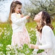 Mother and daughter in field with dandelions — Stock Photo #45538515