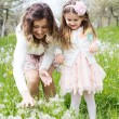 Mother and daughter in field with dandelions — Stock Photo #45571331