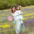 Mother and daughter in field with colorful flowers — Stock Photo #45572235