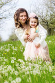 Mother and daughter in field with dandelions — Stock Photo
