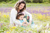 Mother and daughter in field with colorful flowers — Stockfoto