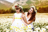 Mother with her child playing in camomile field — Stock Photo