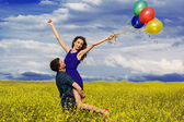 Happy couple with balloons on the yellow field — Stock Photo