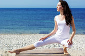 Chica haciendo ejercicios de yoga en la costa del mar — Foto de Stock
