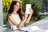 Girl spending time in a cafe using digital tablet — Stock Photo