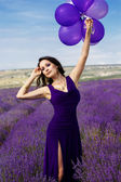 Adorable girl with purple balloons. — Stock Photo
