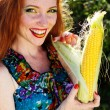 Smiling girl with freckles holding corn cob — Stock Photo #50633109
