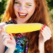 Smiling girl with freckles holding corn cob — Stock Photo #50633147