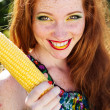 Smiling girl with freckles holding corn cob — Stock Photo #50633179