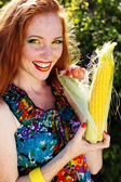 Smiling girl with freckles holding corn cob — Photo