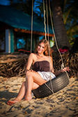 Woman sitting on the swing on paradise beach — Stock Photo