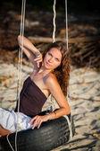 Woman sitting on the swing on paradise beach — Stock Photo