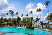 Open-air swimming pool among palm trees — Stock Photo
