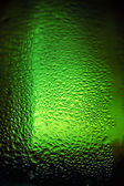 Water drops texture on the green bottle — Stock Photo