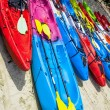 Colorful kayaks lined in a row on a white sand beach — Stock Photo #47297609