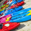 Colorful kayaks lined in a row on a white sand beach — Stock Photo #47297953