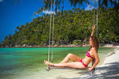 Young woman swings on a tropical beach — Stok fotoğraf