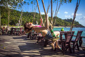 A beautiful girl swings and laughs near beach in cafe. Koh Phangan — Stock Photo