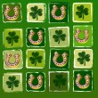 Horseshoes and shamrocks in squares over green background — Stock Photo