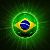 Football with Brazilian flag over green rays — Stock Photo
