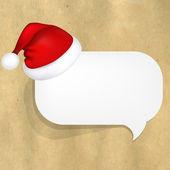Estructura de cartón con papel blanco discurso burbuja y santa sombrero — Vector de stock