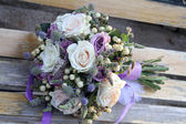 Wedding bouquet on a wooden bench — Stock Photo