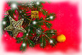 Christmas decorations and fir branch on red background — Стоковое фото